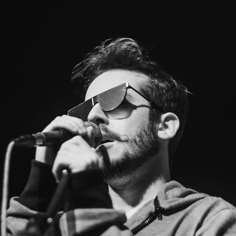 Imagem de divulgação oficial de Jimmy Andrade em preto-e-branco. Artista, de óculos, canta segurando um microfone