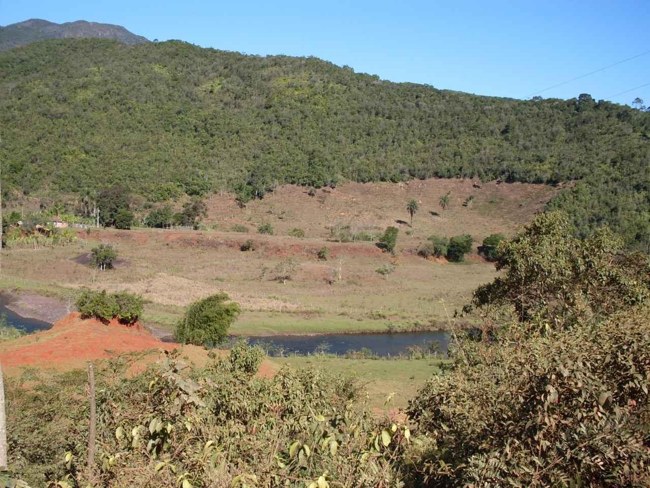 Vale do Rio Conceição, afluente do Rio Doce no Quadrilátero Ferrífero, com sua planície de inundação (junto ao rio) e patamar correspondente a um de seus terraços fluviais (ao fundo)