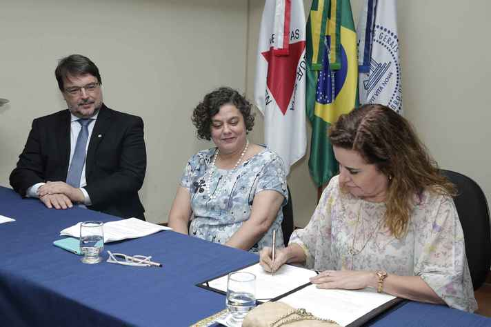 Hugo Cerqueira e a ex-diretora, Paula Miranda, observam assinatura do termo de posse pela reitora Sandra Goulart Almeida