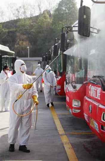 Funcionários chineses desinfetam os ônibus em Yichang, província de Hubei, na China