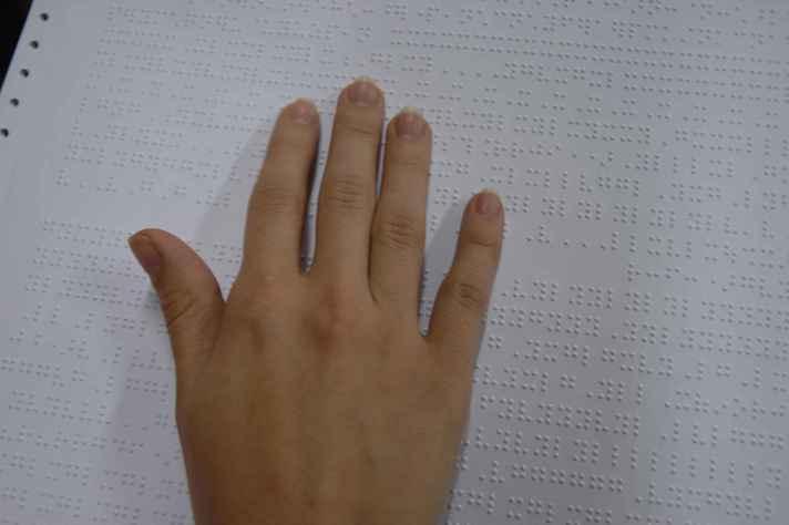 Deficiente visual lê texto em braille: