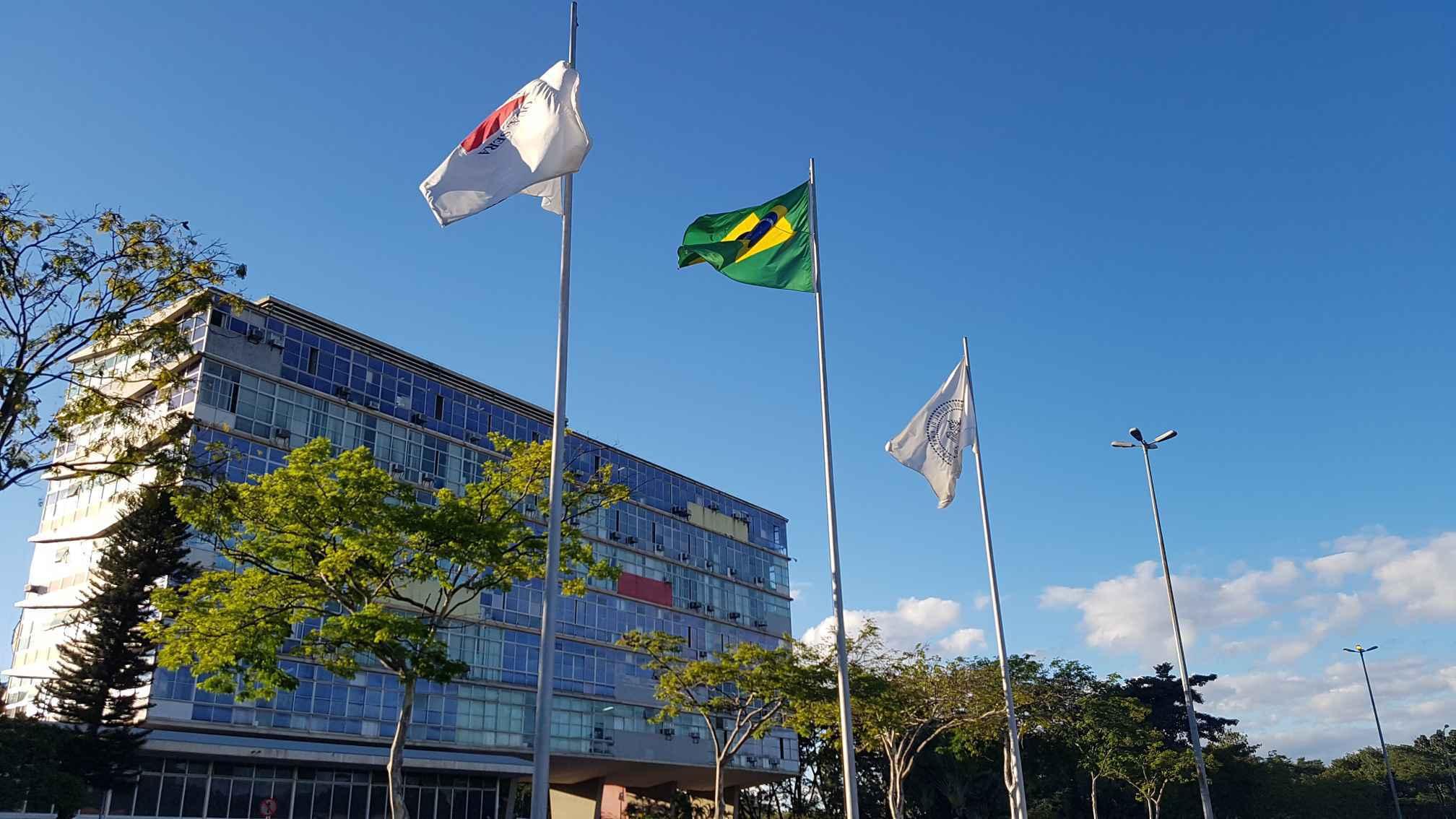Bandeiras de Minas, do Brasil e da UFMG tendo ao fundo o prédio da Reitoria, no campus Pampulha