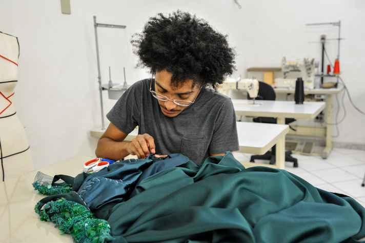 Estudante costura um vestido no ateliê do curso de Design de Moda.