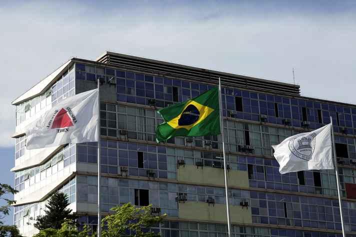 Bandeiras de Minas Gerais, do Brasil e da UFMG hasteadas diante do prédio da Reitoria