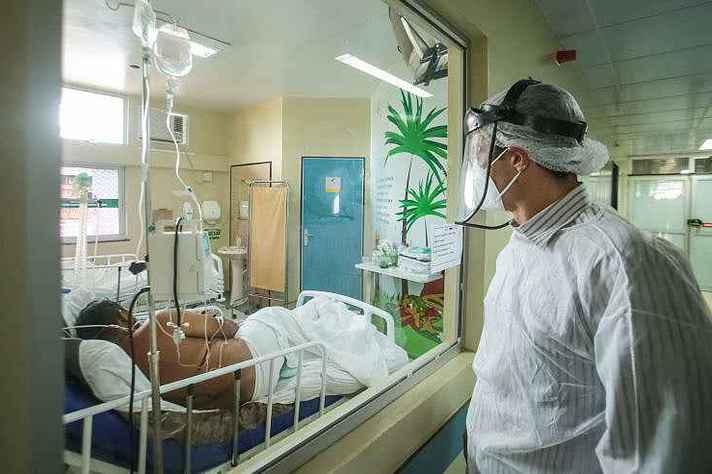 Profissional de saúde observa paciente em UTI em hospital no Pará