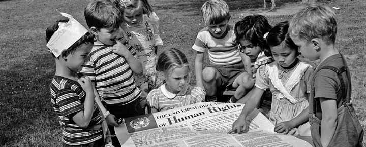 Crianças lendo a Declaração Universal dos Direitos Humanos, após sua adoção