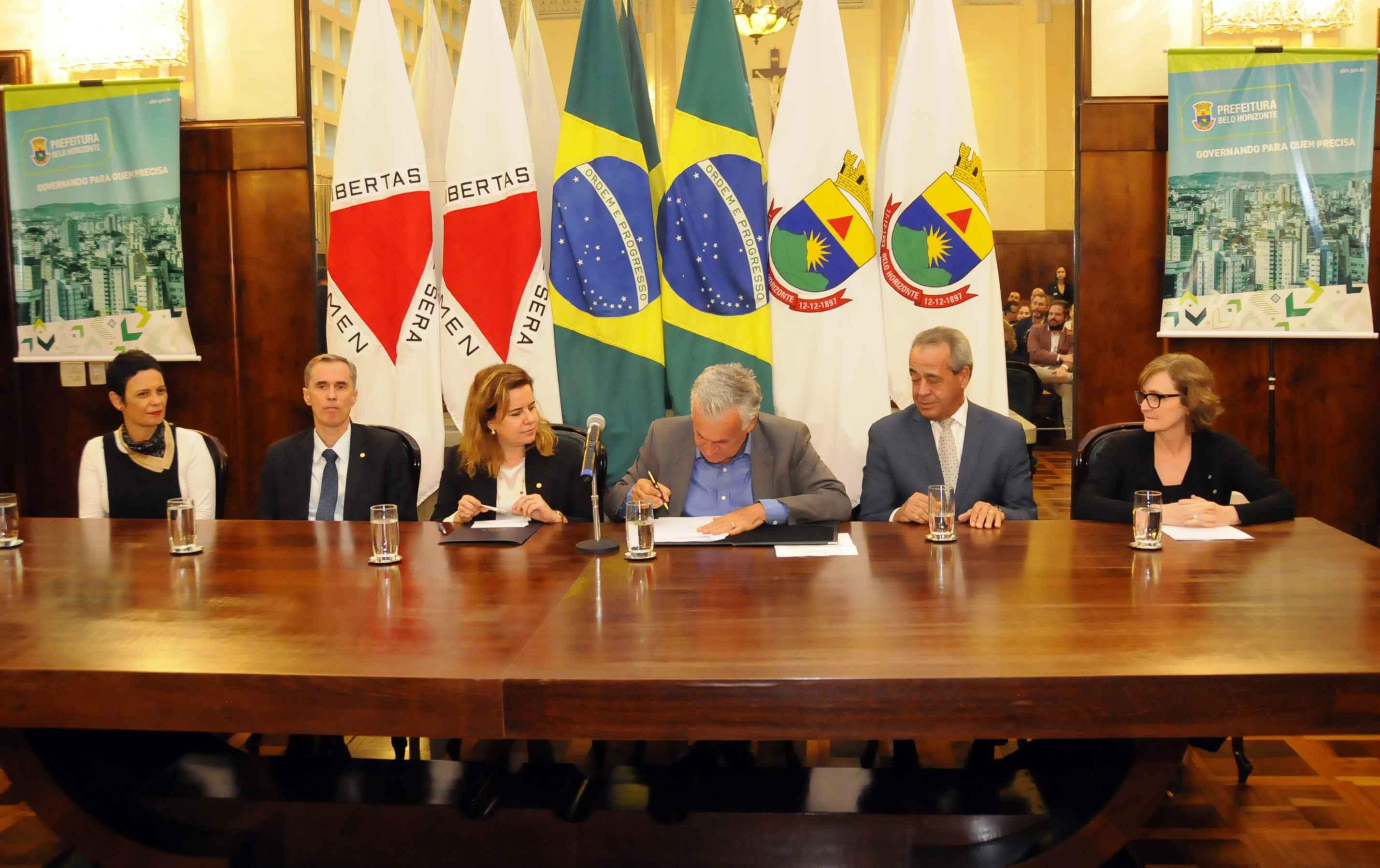 O secretário Juca Ferreira assina o acordo observado pela reitora Sandra Goulart Almeida; compuseram a mesa a pró-reitora de Extensão, Cláudia Mayorga, o vice-reitor Alessandro Fernandes Moreira,