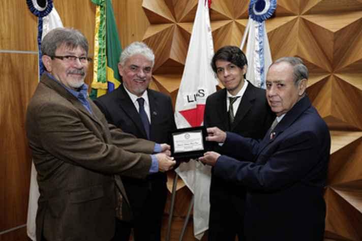 Os professores Roberto Galery, Vicente Tadeu Lopes e Rodrigo Lambert com o homenageado (à direita)
