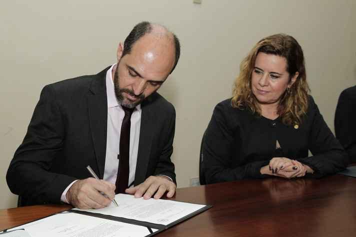 O novo diretor assina o termo de posse observado pela reitora Sandra Goulart Almeida