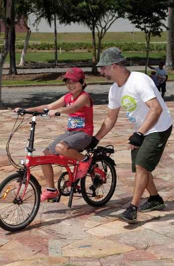 Voluntário do Bike Anjo orienta criança em sua bicicleta