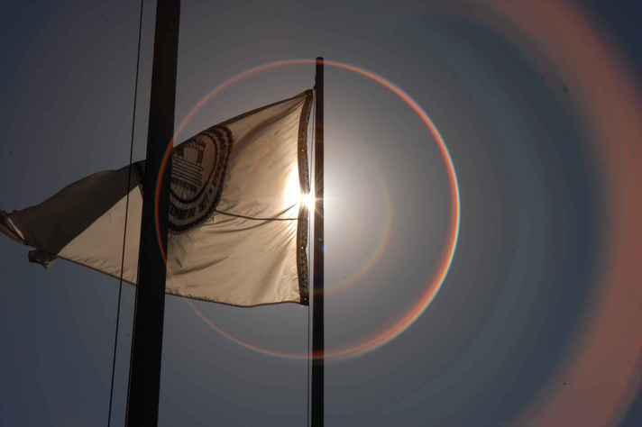 Bandeira da UFMG, hasteada no campus Pampulha, sob a luz do sol