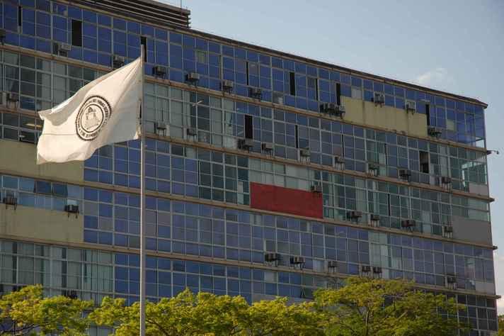 Bandeira da UFMG com o prédio da Reitoria ao fundo: