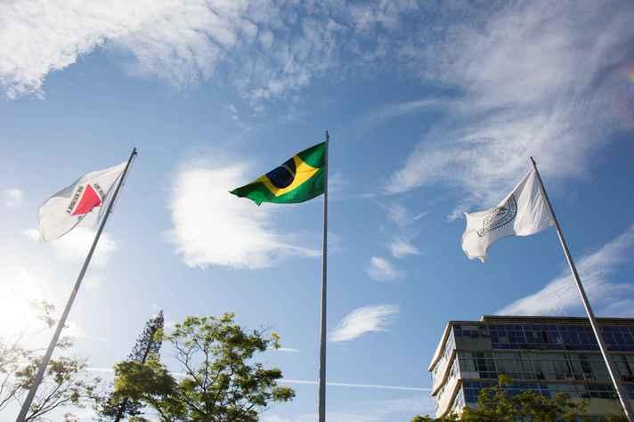 Bandeiras de Minas Gerais, do Brasil e da UFMG hasteadas em frente ao prédio da Reitoria