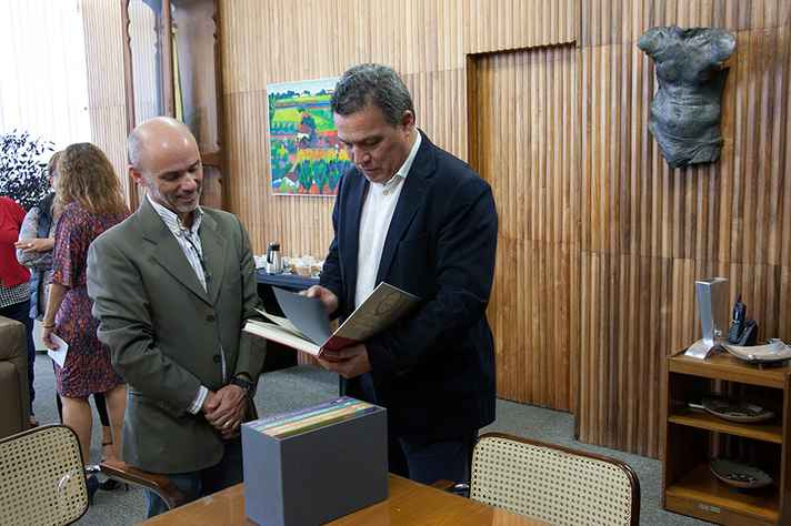 Ao lado de Robson Sávio, Jaime Ramírez folheia volume do relatório da Comissão