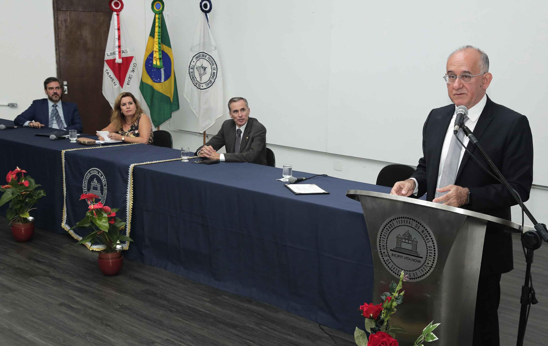 Emerson Silami Garcia discursa observado pelos integrantes da mesa: