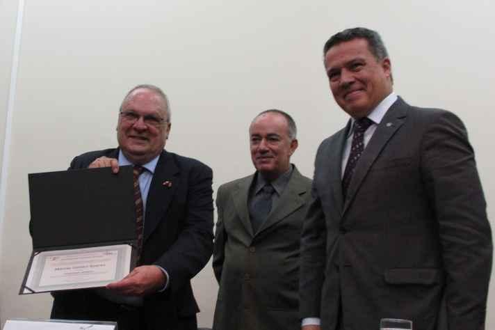 Márcio Soares (com o diploma), o diretor do Icex, Antonio Flávio de Carvalho, e o reitor Jaime Ramírez