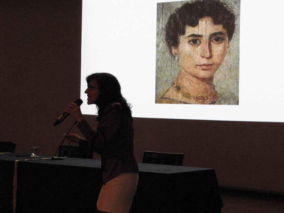 Márcia Barbosa com o retrato da filósofa e matemática grega Hipátia de Alexandria ao fundo:
