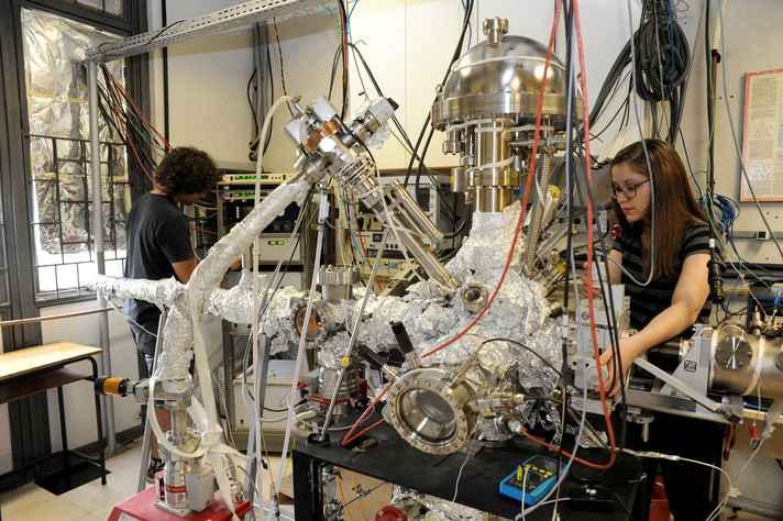 Pesquisadores trabalham com equipamento de espectroscopia de fotoelétrons, em laboratório de física de superfície, no Departamento de Física