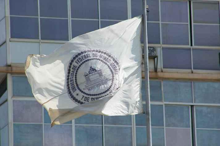 Bandeira da UFMG em primeiro plano com prédio da Reitoria ao fundo