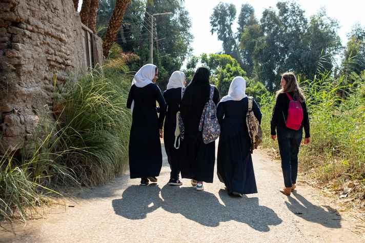 Professora Mariana Petry (à direita) caminha com adolescentes egípcias na periferia de Luxor