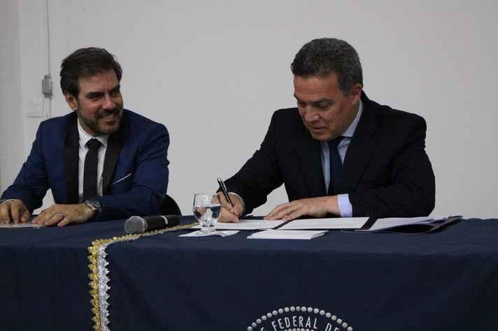Reitor Jaime Ramírez assina o termo de posse, observado por Gustavo Côrtes