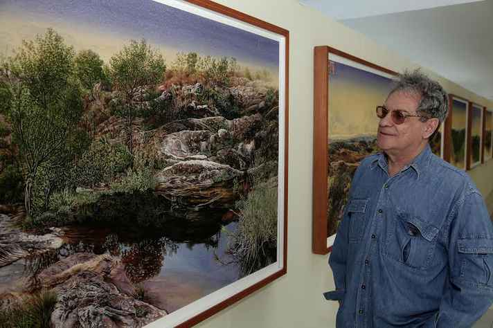 Mario Zavagli observa um dos quadros da exposição