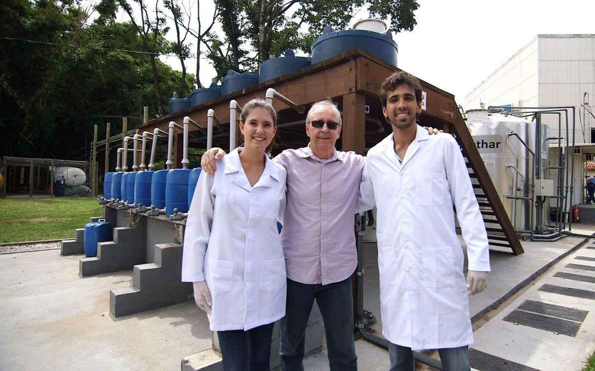 Professor Carlos Chernicharo, orientador do trabalho, entre os estudantes Catarina Azevedo e Augusto de Assis Temponi; ao fundo, a planta de metanização