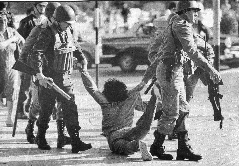 Integrantes da guarda de infantaria detém manifestante na marcha organizada pela Confederação Geral do Trabalho, em março de 1982, em Buenos Aires