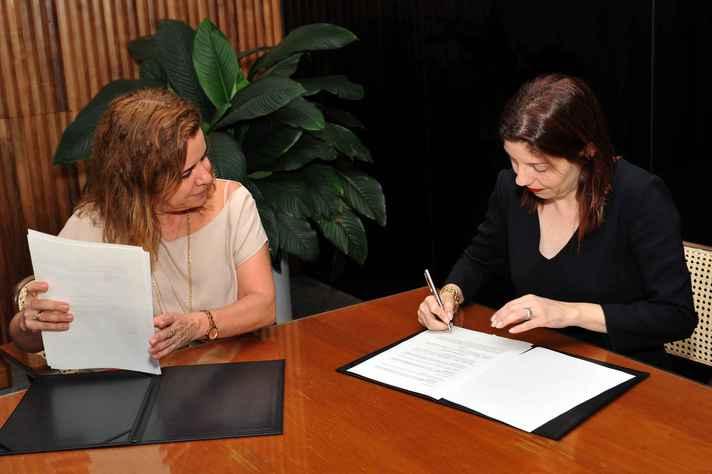 Após a reitora Sandra Goulart Almeida, Eliane Parreiras, presidente da Fundação Clóvis Salgado, assina protocolo de intenções