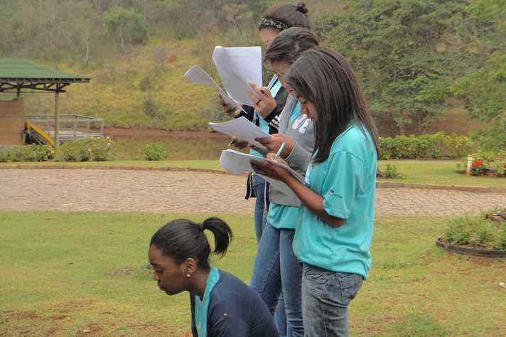 Jovens analisam dados nas imediações de um curso d´água