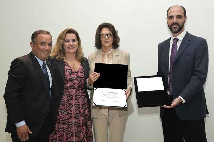 Heloiza Schor com o diploma de emérito entre o diretor do ICEx, Francisco Dutenhefner, a reitora Sandra Goulart Almeida e o professor Rubén Dario Sinisterra