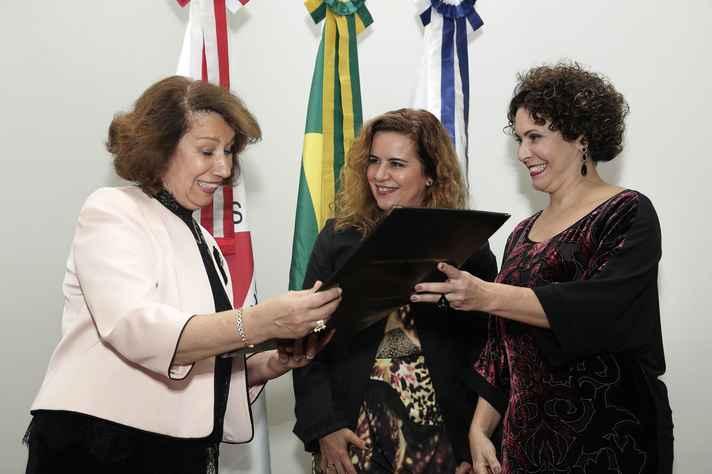 Maria das Graças Carvalho receb o título de Sandra Goulart Almeida (ao centro) e Leiliane Coelho André