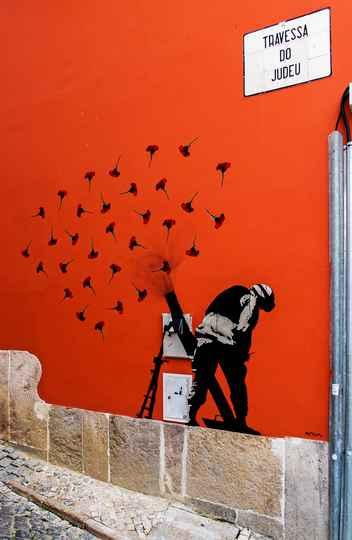 Mural atribuído a Banksy, em Lisboa, alusivo à Revolução dos Cravos de 1974
