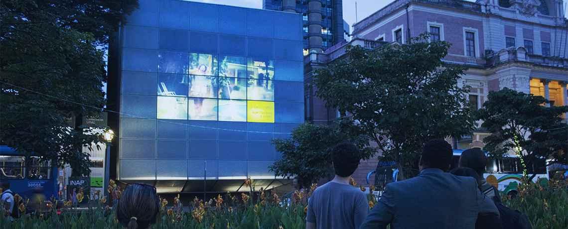 A fachada externa do Espaço do Conhecimento UFMG é revestida por material vítreo que transforma o edifício em uma grande tela de projeção