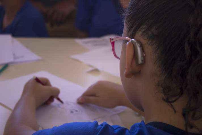 Criança em ação durante oficina de cartuns em libras, em 2017