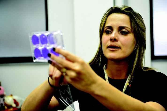 Vivian Costa exibe placa com a qual analisa a quantidade de partículas virais recuperadas de uma amostra