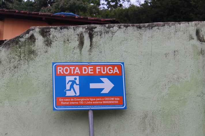 Placa em Macacos sinaliza para rota de fuga em caso de desastre.