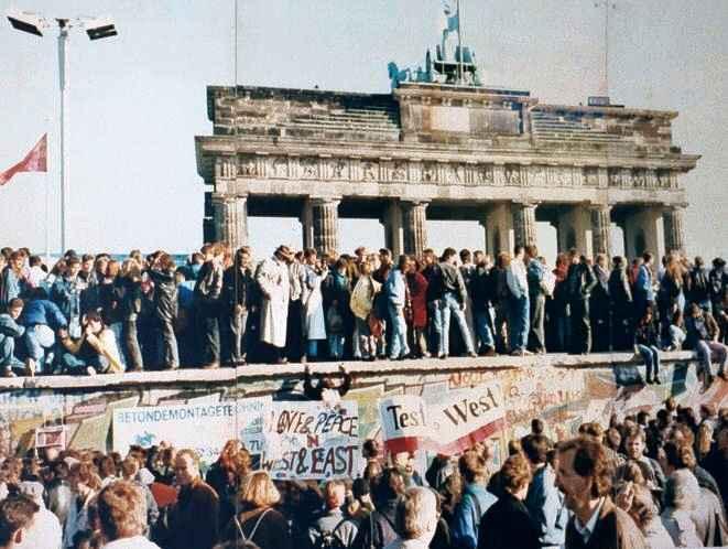 Alemães  em cima do muro, em 1989; destruição começaria no dia seguinte