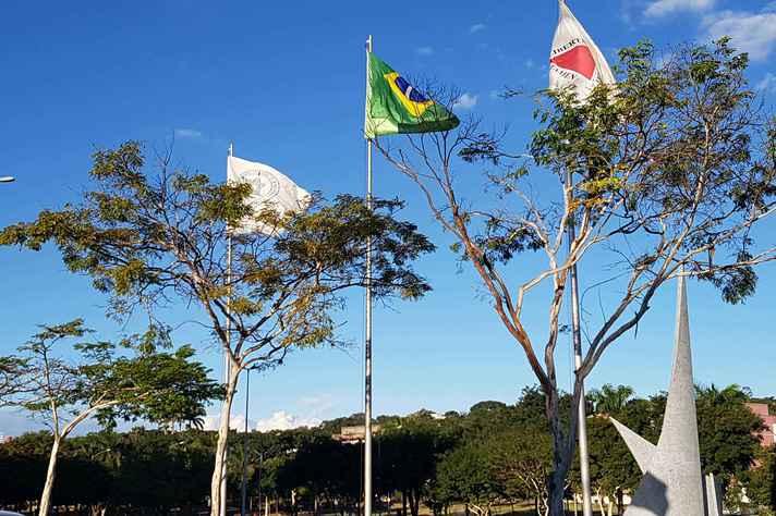 Bandeiras da UFMG, do Brasil e de Minas Gerais hasteadas no gramado da Reitoria