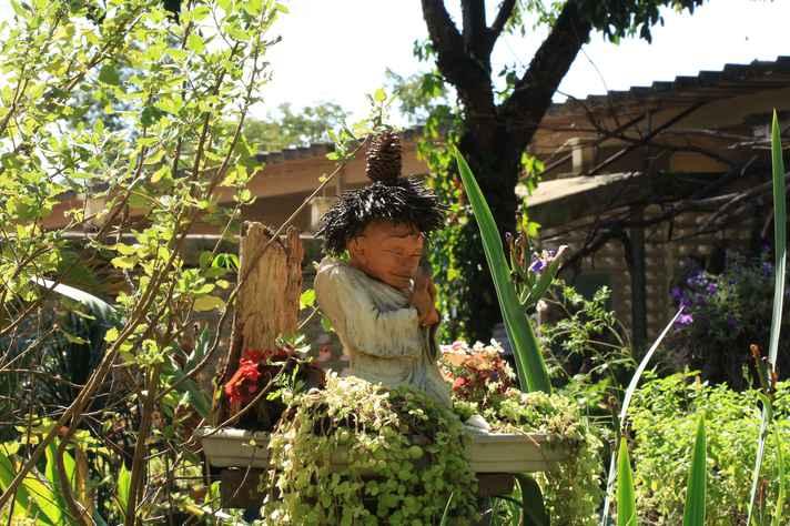 Pequena escultura de um monge no Jardim Mandala, na Faculdade de Educação da UFMG
