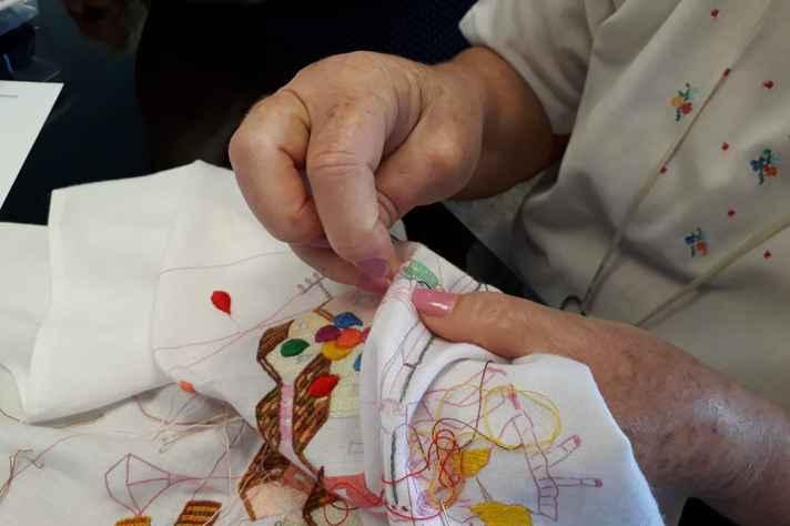 Registro da oficina de bordado. Participante borda releitura de uma obra de Heitor dos Prazeres
